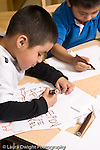 Education preschool 4 year olds art activity literacy boy writing letters with marker another boy drawing in the background vertical