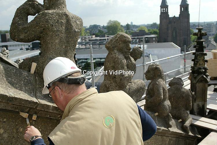 Foto: VidiPhoto..ARNHEM - In Arnhem is begonnen met het terugplaatsen van de 64 ornamenten op en aan de zuidzijde van de Eusebiuskerk. De beelden zijn eind vorig jaar verwijderd omdat ze dreigden te verpulveren door de invloed van de zure regen. Nadat ze een drogingsproces hebben ondergaan, zijn ze vervolgens in Duitsland behandeld met een speciale chemische vloeistof, waardoor de buitenkant van de beelden keihard is geworden. De ornamenten aan de andere zijden van de kerk komen later een de beurt. In totaal gaat het om enkele honderden beelden.
