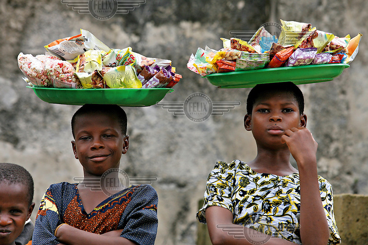 Two children selling snacks, carry their merchandise on trays balanced on their heads in a market in Ikang.