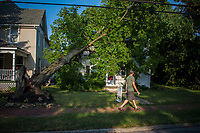 A passerby looks over storm damage to a house on North State Street in Westerville, Ohio, three days after a storm felled trees and power lines leaving as many as 1 million people without power in Ohio. This house, occupied and for sale when the storm struck, is still waiting for an insurance adjuster to complete the damage claim although neighbors speculate the damage to be so severe that the house might not be repaired but torn down.