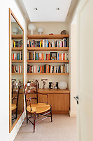 An antique chair is placed in front of a built in cupboard with book shelves above. A full length mirror on the adjacent wall gives a sense of space. A wooden cabin style summer house in the garden of a town house.