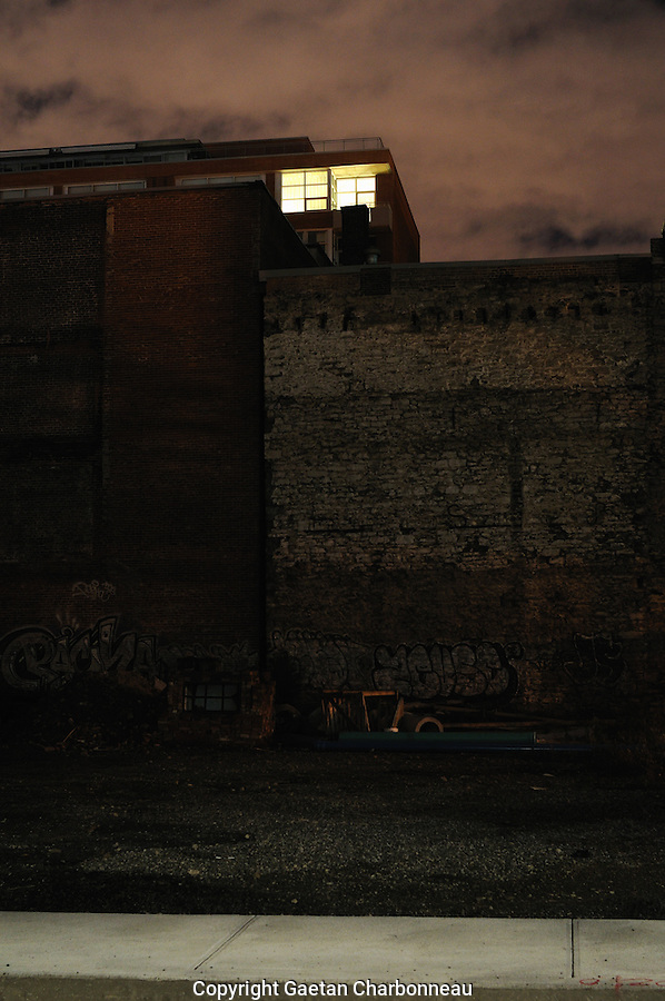 An illuminated window in a brick building, at night.