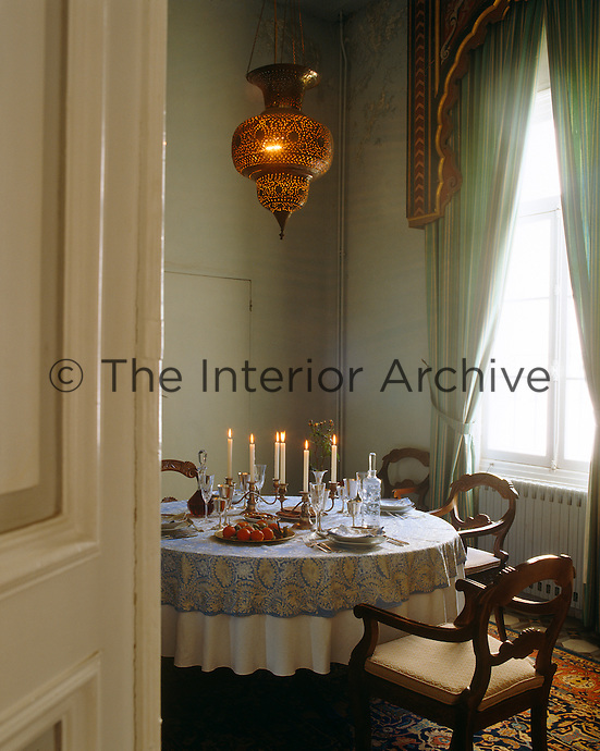 A small dining room with a Moorish lantern hanging above a round table glimpsed through an open door