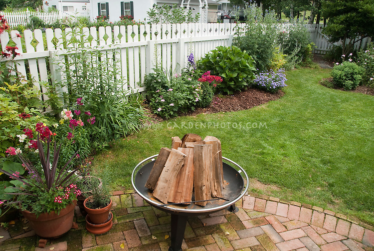 Cooking Fire in Backyard with brick patio, Adirondack chair, plants and flowers