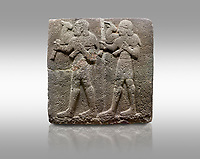 Picture & image of Hittite monumental relief sculpted orthostat stone panel of a Procession Basalt, Karkamıs, (Kargamıs), Carchemish (Karkemish), 900-700 B.C.  Anatolian Civilisations Museum, Ankara, Turkey. Young male servants of Kubaba while carrying sacrificial animals on their shoulders. <br /> <br /> Against a gray background.