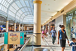 Garden City, New York, USA. 15th August 2013. During BACK AT IT Back-to-School event at Roosevelt Field shopping mall, families and other shoppers shop. At left is Back At It sign, which can be seen from the ground floor and second floor levels, at the mall which is one of the 10 biggest malls in the United States of America.