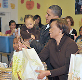 Washington, D.C. - November 25, 2009 -- Marion Robinson, right, hands a bag as United States President Barack Obama holds a baby and daughter Sasha looks on as the First Family hands out food to the homeless at Martha's Table in Washington, D.C. on Wednesday, November 25, 2009..Credit: Ron Sachs / Pool via CNP