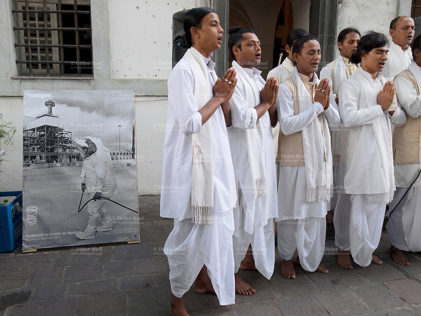 Switzerland. Canton Valais. Martigny. Monk Dancers of Majuli from India sing at the opening of Vestiges exhibit at Manoir de la Ville, Martigny. Poster from the photographer Didier Ruef with a picture taken in Usa, Utah, Deseret chemical depot, Chemical weapons destruction. 28.06.12 © 2012 Didier Ruef
