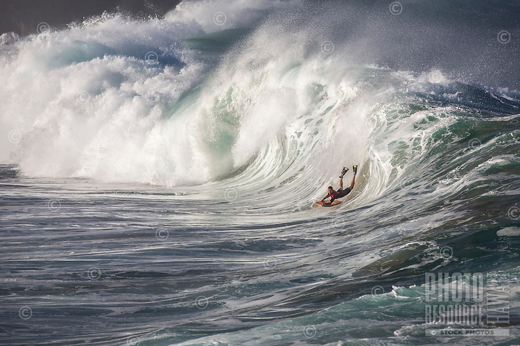 A bodyboarder rides a big hollow wave at Waimea Shorebreak, North Shore, O'ahu.