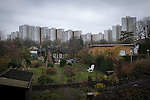 Allotment gardens and tower blocks in Alt-Treptow seen from the course of the former Berlin Wall. The route of the Wall, which stood from 1961-1989, has been developed into the 'Mauerweg,' a thoroughfare which traces most of the route of the Wall which encircled the city and divided it into East and West Berlin during the Cold War. In the years following the 1989 civil uprising in the German Democratic.Republic, most of the Wall was removed as part of the reunification strategy which united the pro-Soviet DDR and the Federal Republic of (West) Germany.