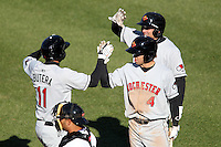 Rochester Red Wings catcher Drew Butera #11 is greeted at home by Brian Dozier #4 and Matt Carson after hitting a home run during the opening game of the International League season against the Rochester Red Wings at Alliance Bank Stadium on April 5, 2012 in Syracuse, New York.  Rochester defeated Syracuse 7-4.  (Mike Janes/Four Seam Images)