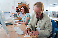 Journalists learning extra skills (setting up a website) at the National Union of Journalists training centre, London.  Using both new technology, Apple Macs, and old technology, fountain pen to make notes.