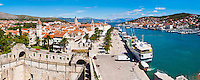 Panoramic photo of Trogir water front, Obala Bana Berislavica, Trogir, Dalmatian Coast, Croatia, Europe. This panoramic photo of Obala Bana Berislavica, the main road along the water front in Trogir was taken from Kamerlengo Fortress (Gradina Kamerlengo). It shows Kamerlengo Fortress (Gradina Kamerlengo) in the foreground and from right to left, the three main Cathedral bell towers that are visible are; Church and Monastery of St Dominic, Cathedral of St Lawrence and St Michael Monastery Church Bellfry. Trogir is a beautiful old town on the Dalmatian Coast of Croatia and is on the UNESCO World Heritage List thanks to it's stunning Romanesque Cathedral's and architecture. Inside the walls of the old town Trogir, the cobbled streets are complemented by beautiful buildings and towering spires. After visiting the many sites, there is always the option of a walk along Obala Bana Berislavica, the main street along the waterfront in Trogir that runs alongside the bright blue Adriatic Sea of the Dalmation Coast of Croatia.