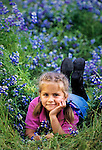 Young girl laying in a field of Lupine Wildflowers.San Luis Obispo, California