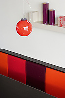 A red pendant light hangs over the dining table and its upholstered striped banquette