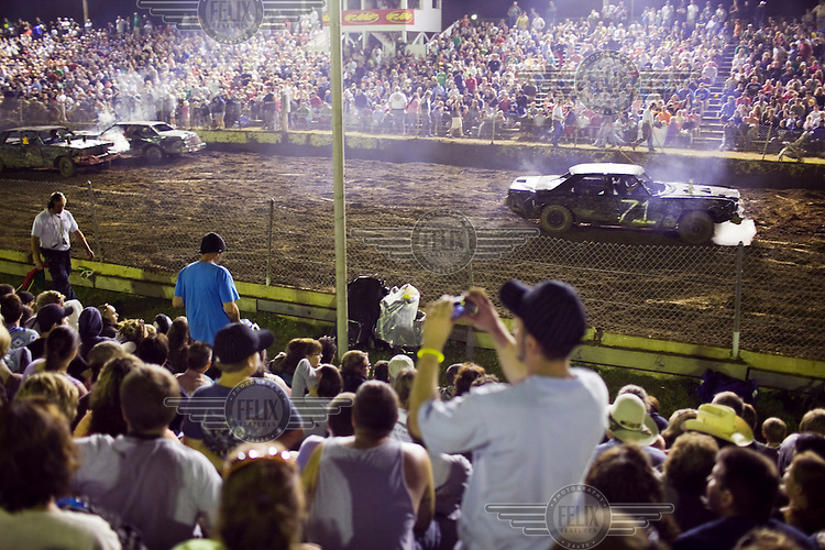 """A spectator takes a picture at """"Smash Your Clunker"""" Demolition Derby, an annual competition, at the Hopkinton State Fair in Hopkinton, New Hampshire. Competitors this year have had an especially difficult job finding big, old, American cars to compete with because of the Cash for Clunkers program."""