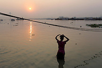 A woman bathes in the Ganges River at sunset in Kolkata.<br />