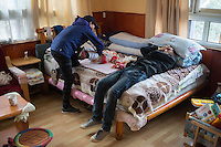 Blind Tibetan Headmaster Nyima Wangdu of the School for the Blind In Tibet rests as wife Yudon changes nappy for their daughter Tenzin Dichen at home inside the campus in the capital city of Lhasa, September 2016.