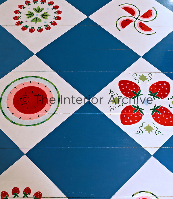 The floorboards of the kitchen are painted in blue and white squares with red motifs depicting strawberries and watermelons