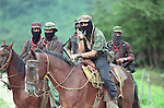 Zapatista sub commander Marcos shown smoking his trademark pipe on top of his horse during an impromptu press conference at his stronghold of La Realidad in the jungles of Chiapas, Mexico shortly after the Zapatista uprising of New Year's Day, 1994. To his right is commander Tacho.