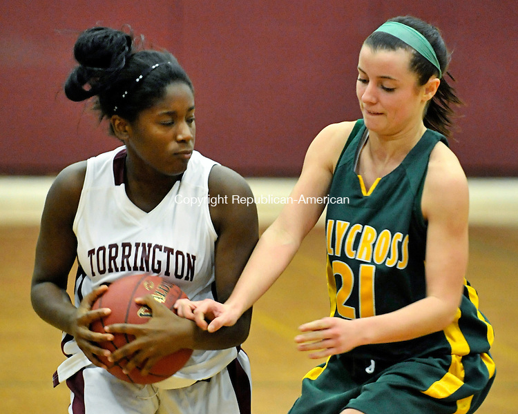 TORRINGTON, CT - 12 December 2012-121212EC10--    Torrington's Mika Howard keeps the ball away from Holy Cross' Melissa Grocki Wednesday night.  Torrington beat the Crusaders, 65-35.  Erin Covey Republican-American.