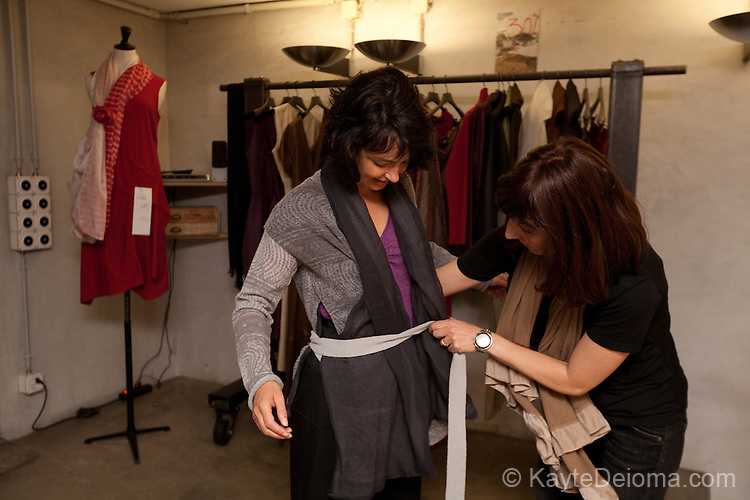 A shop-keeper in a dress shop in Carouge, Geneva, Switzerland helps a woman tie a sash on a designer top.