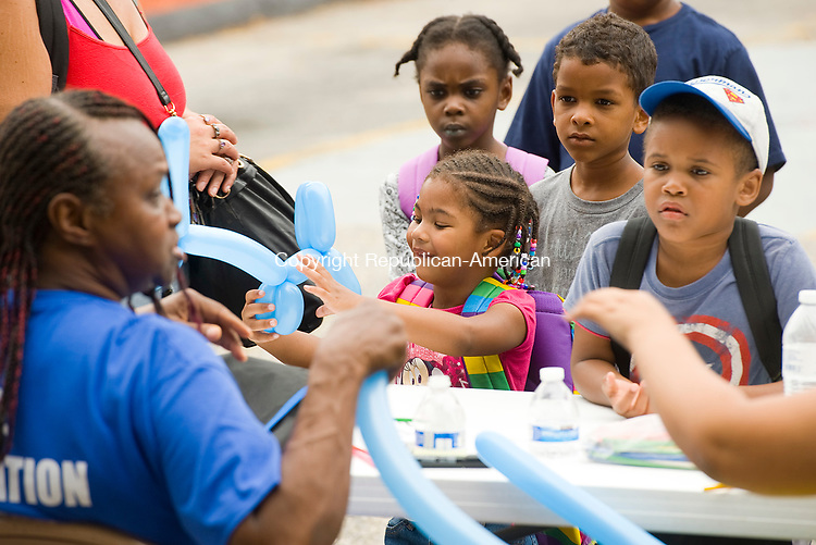 WATERBURY, CT-081217JS02-- Children, including Catalaya Altu, 3, center, line up for balloon toys during the second annual Grace Baptist Church Community Day and Back-to-School give away Saturday at the Grace Baptist Church in Waterbury. Children were given backpacks filled with school items along with a picnic and games. Catalaya will be attending the Pre-K program at Driggs School this fall. <br /> Jim Shannon Republican-American