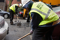 David Dollosa (left) and Aroll Victor fill potholes with asphalt while working for the Boston Public Works Department in Boston, Massachusetts, USA, on April 12, 2012. The city uses a computer system to track public complaints and record work done by city crews to mitigate these complaints.  A supervisor or inspector photographs before and after pictures of the work in addition to making notes about the work done.
