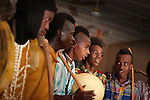 "In the town of Djibo in northern Burkina Faso, young ""doohoobe"" (people who sing ""doohaali"") dance in traditional fashion. The men and women each form a line facing each other, rhythmically shuffling towards and then away from each other. The women clap their hands and sing as the men ""dooho,"" or sing a distinct, deep rhythmic chant. The men hold ""cabbi,"" sticks which are used when herding cattle. ""Doohaali"" is a distinct form of music practiced only by the Fulani in Djelgooji, a particular area of Burkina Faso. The young men in this image are the winners of a regional music and arts competition, going on to perform at Burkina Faso's 2010 ""Semaine Nationale de la Culture"" (SNC) in Bobo-Dioulasso."