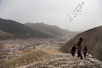 A Tibetan Buddhist boy throws prayer papers into the sky in the hills above Xiahe, Gansu, China.  Xiahe is the home to the Labrang Monastery, one of the most important Tibetan Buddhist prayer sites outside of Tibet.