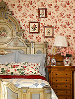An antique bed with an elaborately carved and painted headboard is piled with bedding in blue and white checks and cushions covered in a pattern of red and green geraniums