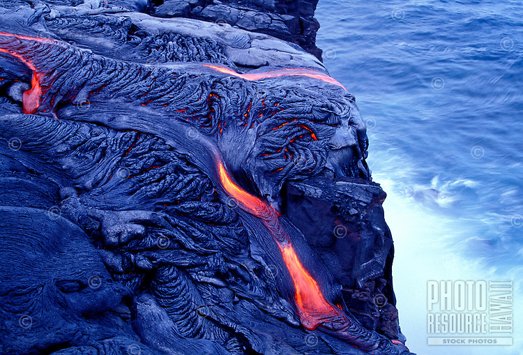 Fiery tongues of red from pahoehoe lava stream into the ocean on the Puna coast of Hawaii Volcanoes National Park on the Big Island.