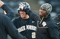 Will Craig (22) of the Wake Forest Demon Deacons is greeted by teammate Kevin Jordan (21) after scoring a run against the Georgetown Hoyas at Wake Forest Baseball Park on February 16, 2014 in Winston-Salem, North Carolina.  The Demon Deacons defeated the Hoyas 3-2.  (Brian Westerholt/Four Seam Images)