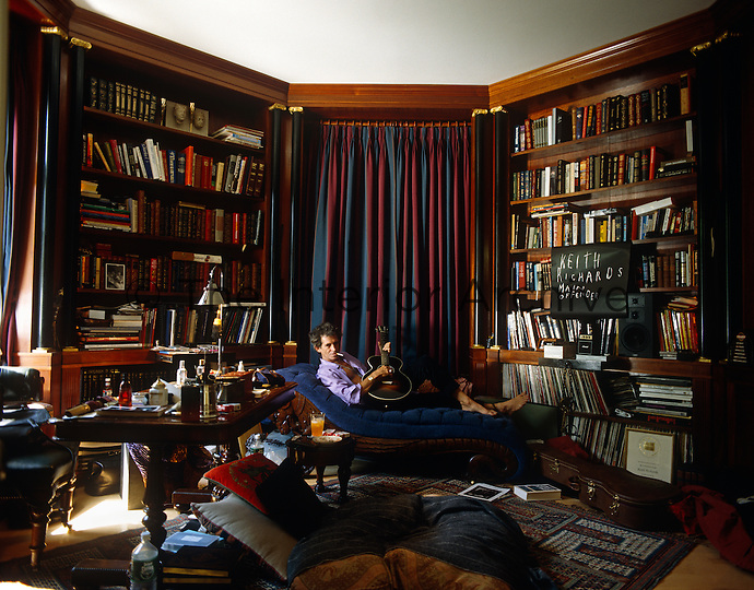 Keith Richard's relaxes on a chaise in his octagonal library surrounded by mahogany bookshelves decorated with classical motifs