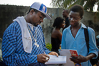 Film actor Emeka Ike signs his autograph in the text book of a school boy who was passing by the set of a Nollywood movie production. Emeka Ike is one of the stars of Nollywood and is regularly recognized on the streets. Big Nollywood stars have fans from Jamaica to Australia.
