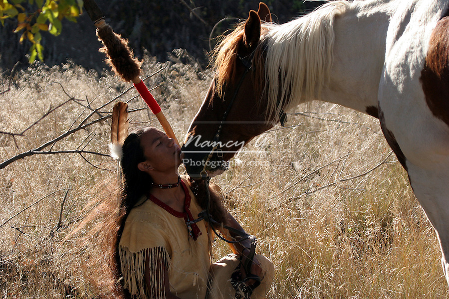 A Native American Indian boy wearing a feather getting a loving nudge from a horse holding a spear with buffalo hide on it