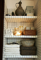 Simple, mosaic clad shelving in the bathroom provides smart, practical storage