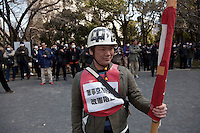 A union activist wearing a helmet and holding a flag stands in front of many security police tasking notes  at a left wing demonstration against the exploitation of farmers during the construction of Narita Airport. Shiba Park, Tokyo, Japan. Sunday March 23rd 2014. The main organiser of the protest was The Farmers' league Against Narita Airport. Around 1,000 activists from this league and other unions took part.