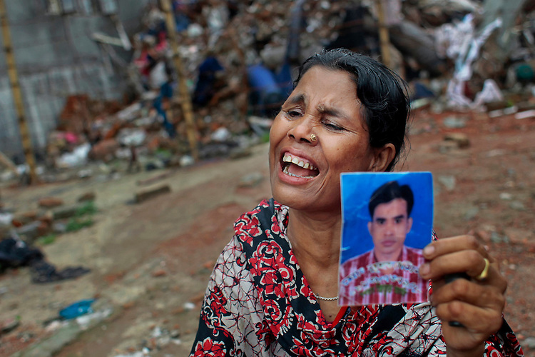 A Bangladeshi woman cries holding a photograph of her son, a victim of the Rana Plaza building collapse that killed 1,129 people, as she joins in a protest demanding that companies sign the Accord on Fire and Building Safety in Savar, near Dhaka, Bangladesh, Saturday, June 29, 2013.
