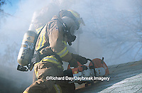 63818-01609 Firefighter using saw to ventilate smoke from house fire  Kinmundy-Alma Fire District,  Kinmundy IL