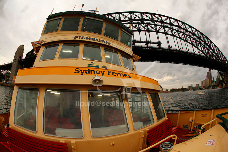 Old Sydney Ferry passing under the Harbour Bridge early in the morning with a grey weather.