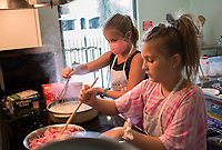"Lily Buck, 9, (from left) and Rachel Sample, 10, stir ingredients for a casserole, Monday, July 27, 2020 during cooking camp for kids at Young Chefs Academy in Bentonville. The academy is hosting a four day cooking camp. The kids gain some culinary experience baking and cooking. They made a casserole, rocky road cookies, Mardi Gras cupcakes, fruit pops and cream cheese frosting. No prior experience is required and kids of all skill levels can participate in the camp. ""Charles, he said he was six. His favorite dish is quiche lorraine,"" said head chef Mary Nieto, praising his culinary knowledge. Check out nwaonline.com/200728Daily/ for today's photo gallery. <br /> (NWA Democrat-Gazette/Charlie Kaijo)"