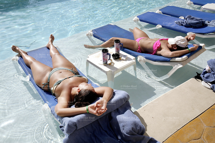 Dominican Republic. La Altagracia Province. Coastal resort of Punta Cana. Hotel Carabela Bavaro. Two white women, both spanish tourists lay on deckchairs in the pool. They sleep, sunbathe and enjoy the sun on their skins. © 2006 Didier Ruef