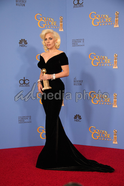 """After winning the category of BEST PERFORMANCE BY AN ACTRESS IN A MINI-SERIES OR MOTION PICTURE MADE FOR TELEVISION for her role in """"American Horror Story: Hotel,"""" actress Lady Gaga poses backstage in the press room with her Golden Globe Award at the 73rd Annual Golden Globe Awards at the Beverly Hilton in Beverly Hills, CA on Sunday, January 10, 2016. Photo Credit: HFPA/AdMedia"""