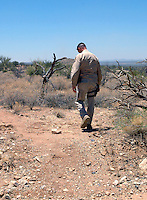 A Border Patrol Agent Tracking foot prints ledt behind Illegals crossing the desert south of Tucson, AZ. This photo was taken during a ride along with Borstar Border Patrol Agents south of Tucson..Photo by AJ Alexander