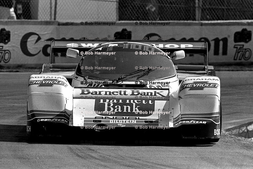 MIAMI, FL - MARCH 2: AJ Foyt drives Preston Henn's Porsche 962 104 during the Lowenbrau Grand Prix of Miami IMSA GTP race on the temporary street circuit in Bicentennial Park in Miami, Florida, on March 2, 1986.
