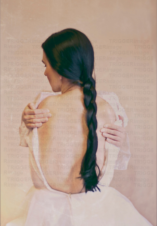 A black haired lady in a white dress sitting in front of a wall back to the camera showing her back with hands with long plait