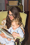 Dark haired Mom sits in chair reading book to blonde pre-schooler son in pajamas in evening