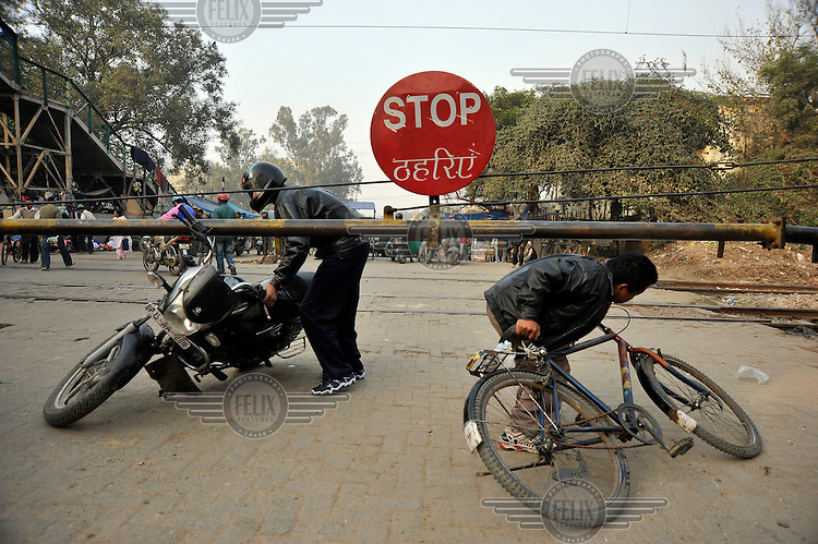 People ignore a stop sign and rush to get their bikes under a barrier before a train passes by.