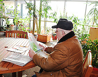 Merle Goth reads the newspaper in the sunny atrium of the Warner Park Community & Recreation Center